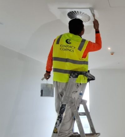 painter painting ceiling with paint brush